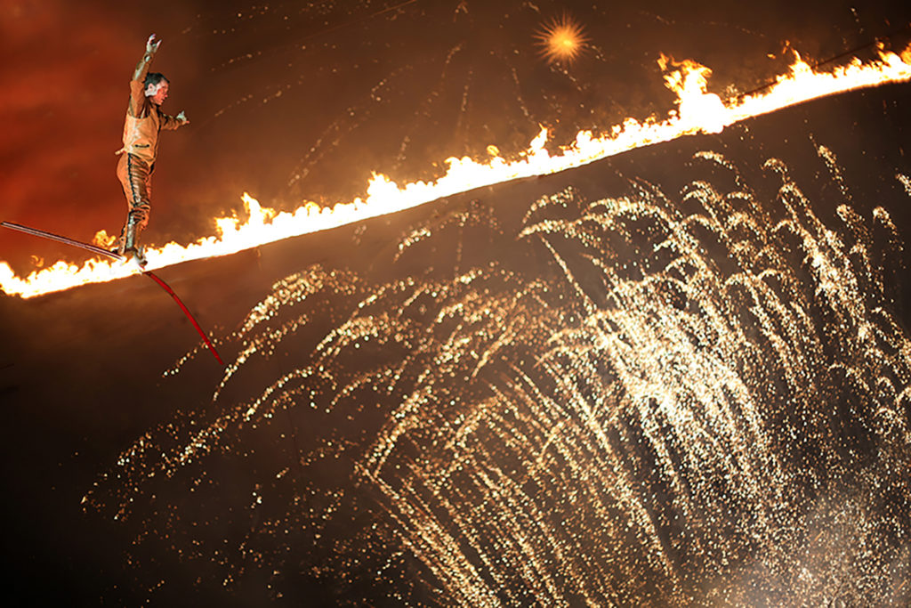 Jade performs on his fire high-wire at the festival of speed in England for Cirque Bijou. a one-of-a-kind stunt.